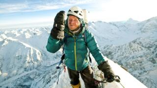 Tomasz Mackiewicz, wearing a green climbing coat, is pictured on top of a snow-white mountain range
