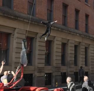 Stuntman hanging from a wire