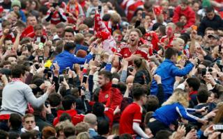 Middlesbrough's Adam Clayton celebrates with fans on the pitch after being promoted