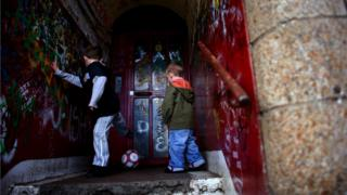 Two young boys play football in the doorway of a run-down building