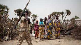 Soldier wey carry RPG dey waka pass where women dey