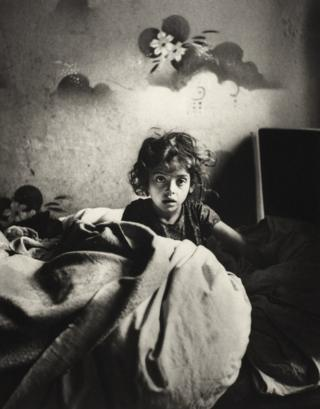 Sara, sitting in bed in a basement dwelling, with stencilled flowers above her head. Warsaw, Poland, c. 1935–37.