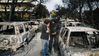 Mulher e integrante da equipe de resgate fazem buscas em meio a carros queimados por incêndio na Grécia, próximo à Atenas, em 24 de julho de 2018