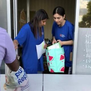 Volunteers hand out bags of food