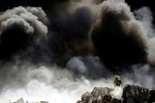 A firefighter works to extinguish the fire at a recycling centre in Ciudad Juarez, Mexico