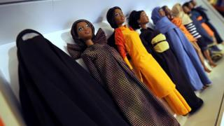 Barbies wearing cultural clothes from around the world, including a Burkha (L), are displayed during a touring exhibition at a book store in downtown Milan on November 29, 2010. The 500 Barbies outfitted by Italian designer Eliana Lorena were part of a charity auction at Sotheby's in London in 2009, in celebration of Barbie�s 50th anniversary. Today each Barbie of this collection cost 180 euros (236 USD).