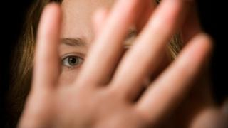 Woman holding up hand over face