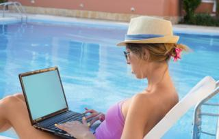 Woman on computer by pool