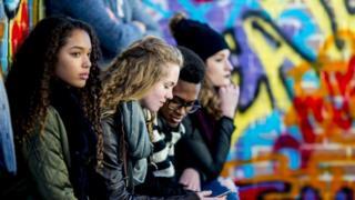 Grupo de jovens em um pátio, observando o entorno e rodeados por grafites