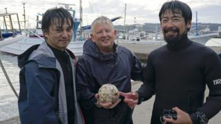 Researchers posing with the cannonball