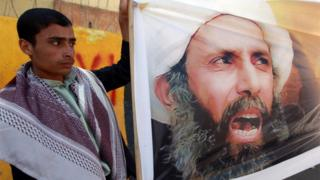 A file picture taken in the Yemeni capital Sanaa on October 18, 2014, shows a protester taking part in a demonstration outside the Saudi embassy against the death sentence on Saudi Shiite cleric and anti-government protest leader, Nimr al-Nimr (portrait), after he was convicted by Saudi authorities of sedition.