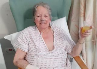 Mary Blessington drinking orange juice in hospital