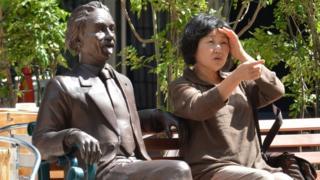 Una señora sentada en un banco con una estatua de Einstein
