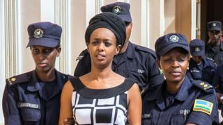 Diane Rwigara (C), a prominent critic of Rwanda's President Paul Kagame, is escorted by Police officers to the court room at the Nyarugenge intermediate court in Kigali on October 9, 2017