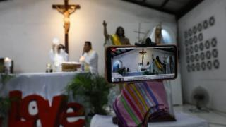 A smartphone is used for online streaming of a Catholic mass to mark Easter Sunday at a church in Quezon City, Metro Manila, Philippines