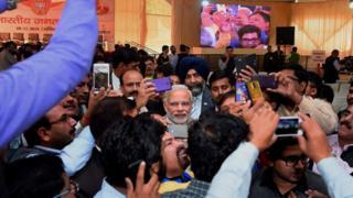पत्रकारों से घिरे प्रधानमंत्री नरेंद्र मोदी