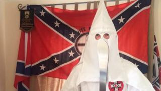 Thomas segura um machete vestido com o traje característico da Ku Klux Klan