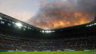 Storm clouds gather over a football stadium