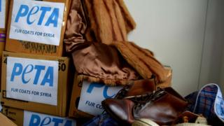 "Boxes reading ""Fur coats for Syria"", fur coats, and leather shoes"