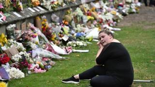 سيدة نيوزيلندية تجلس حزينة أمام آلاف باقات الزهور التي وضعت أمام مدخل المستشفى في مدينة كرايستت تشيرتش.