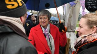 Theresa May under an umbrella while she talks to the public at the Royal Welsh Winter Fair