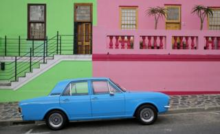 A car is parked outside colored houses of the historic Bo Kaap area of Cape Town, South Africa, 15 March 2018. This former township, situated on the slopes of Signal Hill above the city center, is a historical centre of Cape Malay culture in the city and home to the first mosque in South Africa established in 1884 by immigrant workers. The area is one of the cities biggest tourist attractions.