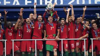 Cristiano Ronaldo hold up the winners' trophy as he celebrates with the team in the Euro 2016 final football match between France and Portugal