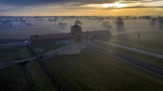 The sun rises over the early morning mist blanketing the barbed wire electrified fence and the Death Gate the Auschwitz II-Birkenau extermination camp on December 18, 2019