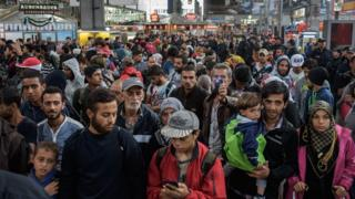 Refugees walk through the main train station in Munich, Germany