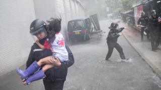 A policeman rescues a small girl in Hong Kong