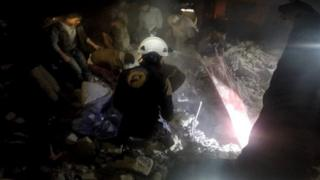 Photo posted by the Syria Civil Defence, also known as the White Helmets, purportedly showing rescue workers after air strikes on Maarshurin, in the Syrian province of Idlib (20 December 2017)