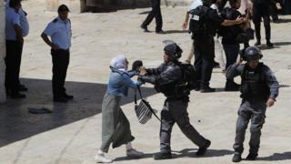 رجل شرطة إسرائيلي يدفع امرأة فلسطينية في المسجد الأقصى صبيحة عيد الفطر