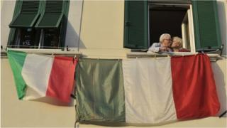 A couple kiss at the window of their home from which flags are displayed during the lockdown in Italy