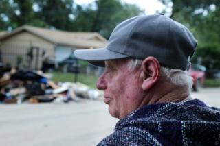 Melvin Lee Rogers surveys the damage outside the home he shares with his brother