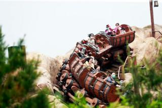 Riders wearing face masks are seen on the Seven Dwarfs Mine Train