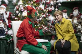Nicola Sturgeon is interviewed by a journalist dressed as a Christmas elf