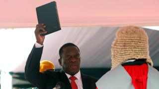 Emmerson Mnangagwa holding up a Bible while being sworn in