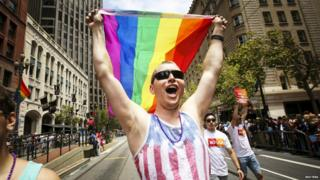 A man waves a rainbow flag while marching in the San Francisco gay pride parade - 28 June 2015