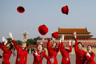 Ushers dressed in red throw their hats in the air.