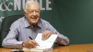 """In this July 7, 2015 file photo, former US President Jimmy Carter signs his new Book """"A Full Life: Reflections at Ninety"""" at Barnes & Noble on 5th avenue in New York 7 July 2015"""