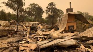 Twisted corrugated iron and brick stacks remain of a home destroyed by fire in Mallacoota
