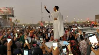 Alaa Salah, gestures (as people film her on their mobile phones) during a protest, along a bridge in Khartoum, Sudan, demanding Sudanese President Omar Al-Bashir to step down, 8 April 2019.