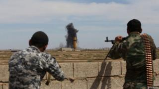 Smoke billows following an air strike as members of the Iraqi government forces hold a position on the western outskirts of Tikrit, on 27 March 2015,
