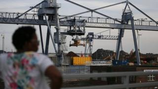 A woman overlooks port works in the town of Tilbury
