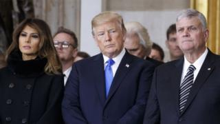 President Donald Trump and first lady Melania Trump stand with Franklin Graham during a ceremony