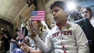 Девочка из Армении приносит клятву на верность Америке на церемонии принятия в гражданство в Бронксе