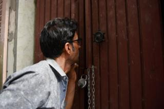 A man peeps inside the house where 11 members of a family allegedly committed suicide on 2 July in Delhi.