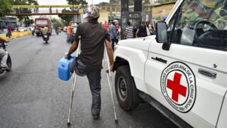 A man walks away after receiving a drum to collect water and water purification tablets from members of the Venezuelan Red Cross in Catia neighborhood in Caracas, Venezuela, on April 16, 2019