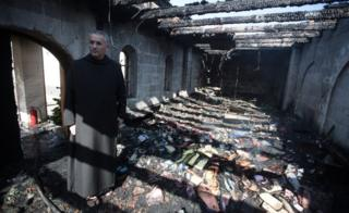 Priest inspects the damage at a room located on the complex of the Church of the Multiplication at Tabgha, on the shores on the Sea of Galilee in northern Israel, on June 18, 2015,