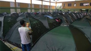 A man holds his baby while looking down a row of tents set up in a shelter